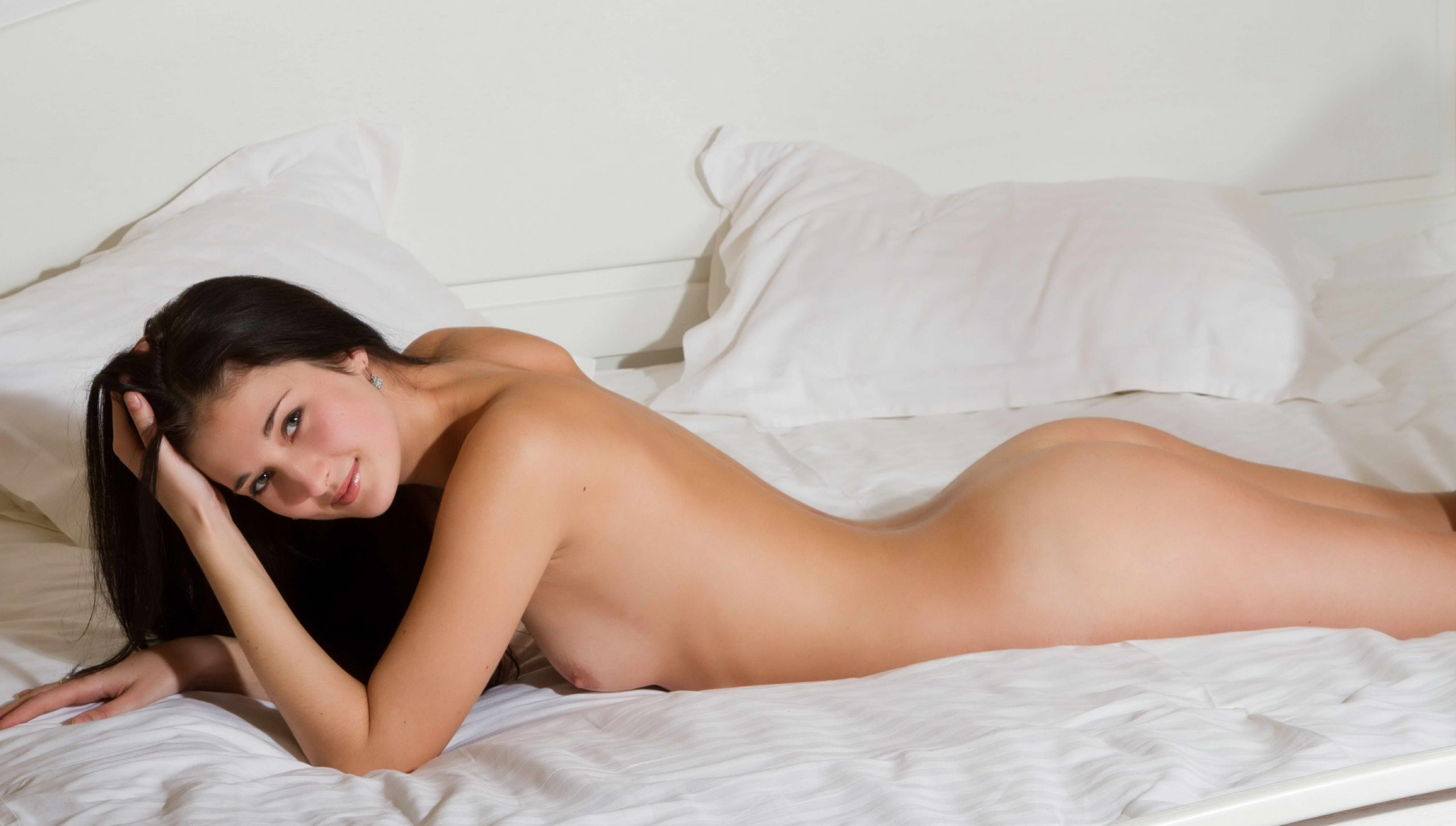 Naked Beauty On Her Belly in a white bed